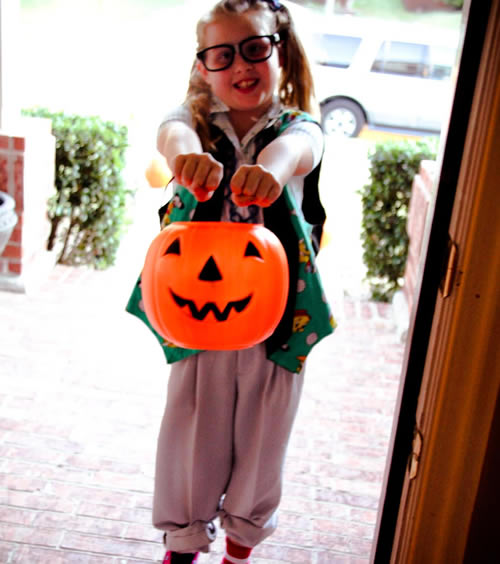 Girl nerd costume with pumpkin pail
