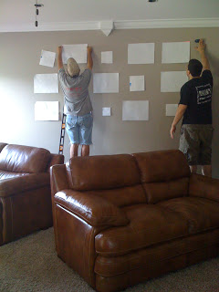 Man using paper templates to layout a gallery wall