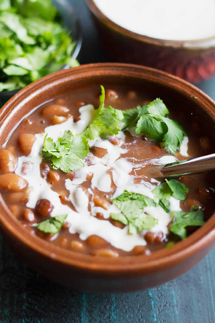 instant pot made pinto beans in a bowl with cilantro sour cream