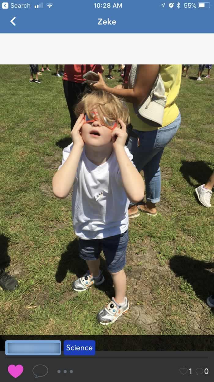 Seesaw app sharing class photos - kid watching eclipse